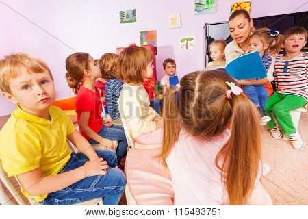 Teacher read book to little boys and girls