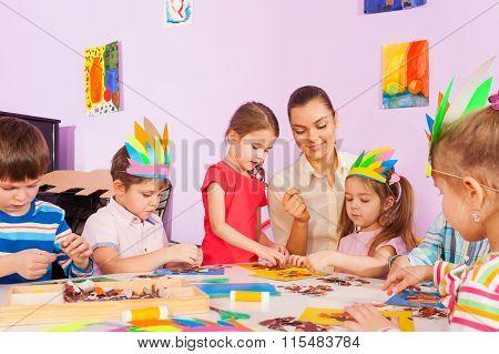 Teacher work with kids in art preschool class