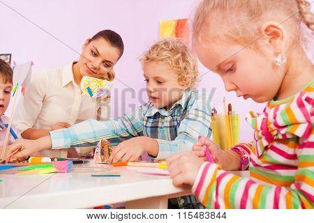 Teacher and little children crafting in class