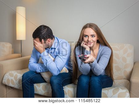 Portrait of couple sitting on sofa watching television.