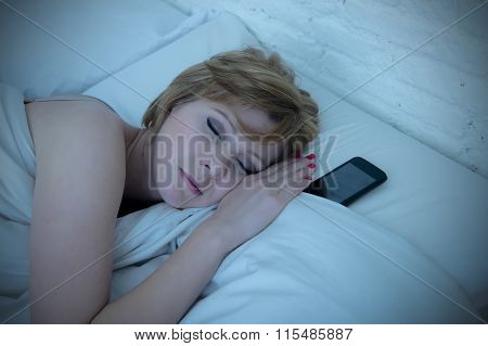 Young Attractive Woman Sleeping In Bed Alone Holding Mobile Phone Next To Her At Night As Addict