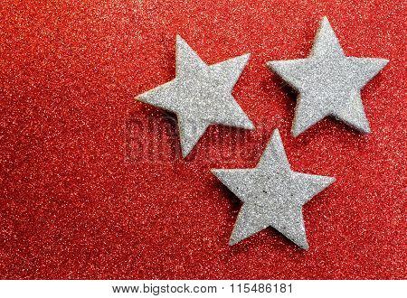 Three Silver Stars On Bright Red Glittery Illuminated Background