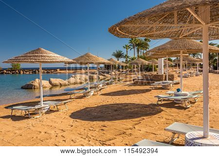Straw umbrellas and sunbeds on the wonderful tropical beach.