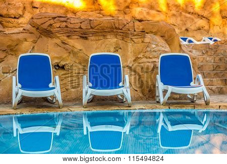 Several of sun loungers by a beautiful swimming pool