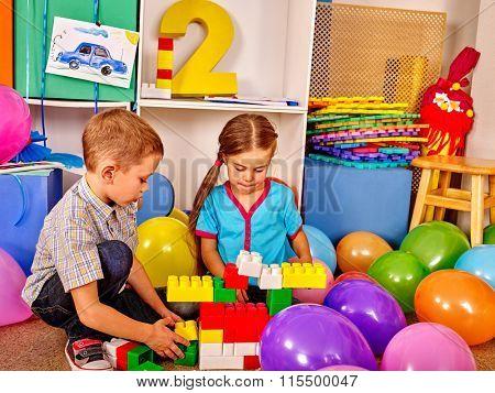 Little boy and girl game blocks on floor in kindergarten . Balloons decoration.