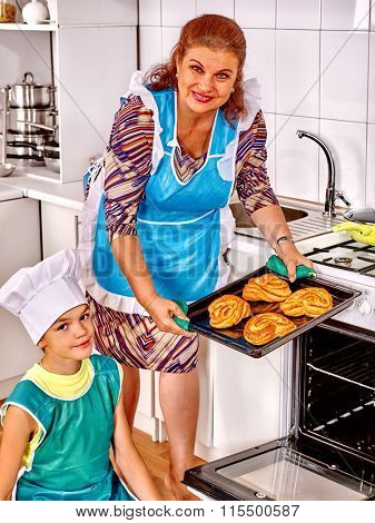 Grandmother and grandson baking cookies at home kitchen.