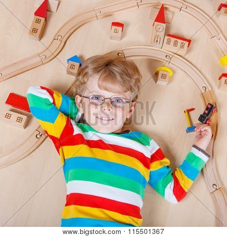 Little blond child playing with wooden railroad trains indoor