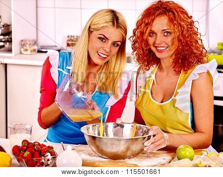 Couple of young women in apron baking cookies in oven.