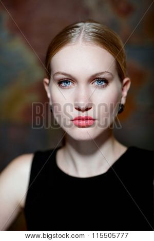 Closeup portrait of beautiful determined nordic woman with blue eyes in makeup.