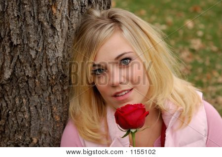 Picture or Photo of Beautiful young woman holding a red rose in autumn.