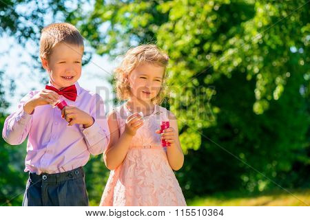 A Boy And His Girlfriend With Soap Bubbles In The Park