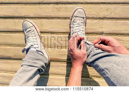 Man Hands Tie Shoes On Wooden Dais Outdoor Going To Work - Young Healthy Hipster Lace Up Sneakers