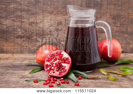 Isolated Pomegranate Juice With Pomegranate On Wooden Background