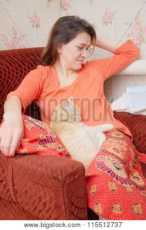 Beautiful Tatar Woman On The Chair Relaxing With Cat And Reading Magaz