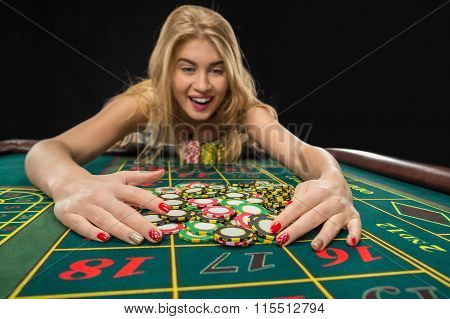Young pretty women playing roulette wins at the casino