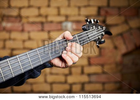 Head Of A Bass Guitar And The Fingers Of The Bassist