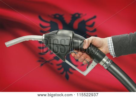 Fuel Pump Nozzle In Hand With National Flag On Background - Albania