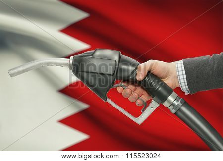 Fuel Pump Nozzle In Hand With National Flag On Background - Bahrain