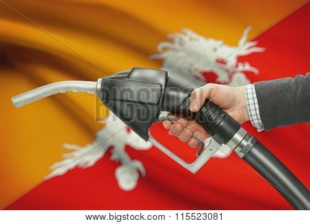 Fuel Pump Nozzle In Hand With National Flag On Background - Bhutan