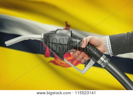 Fuel Pump Nozzle In Hand With National Flag On Background - Brunei