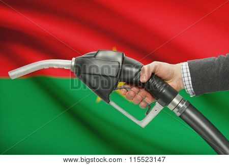 Fuel Pump Nozzle In Hand With National Flag On Background - Burkina Faso