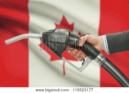 Fuel Pump Nozzle In Hand With National Flag On Background - Canada