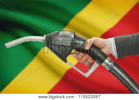 Fuel Pump Nozzle In Hand With National Flag On Background - Congo-brazzaville