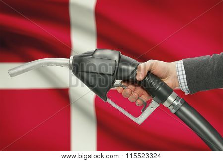 Fuel Pump Nozzle In Hand With National Flag On Background - Denmark