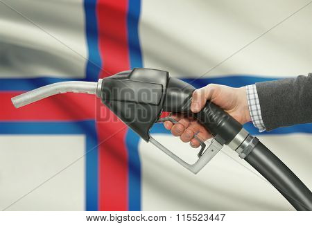 Fuel Pump Nozzle In Hand With National Flag On Background - Faroe Islands