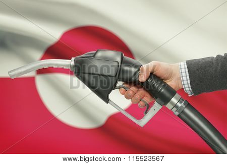 Fuel Pump Nozzle In Hand With National Flag On Background - Greenland