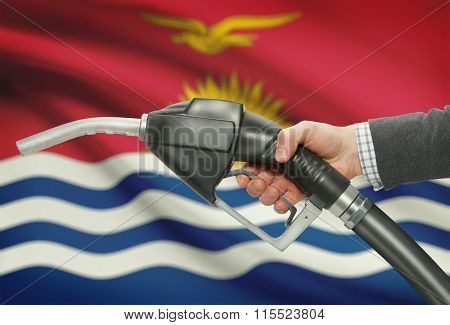 Fuel Pump Nozzle In Hand With National Flag On Background - Kiribati