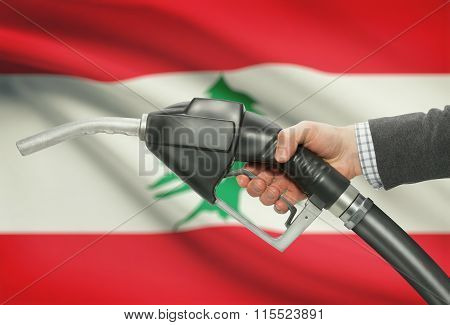 Fuel Pump Nozzle In Hand With National Flag On Background - Lebanon