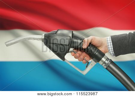 Fuel Pump Nozzle In Hand With National Flag On Background - Luxembourg