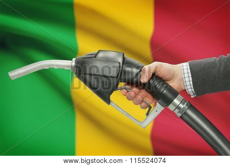 Fuel Pump Nozzle In Hand With National Flag On Background - Mali
