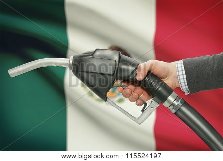 Fuel Pump Nozzle In Hand With National Flag On Background - Mexico