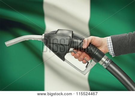 Fuel Pump Nozzle In Hand With National Flag On Background - Nigeria