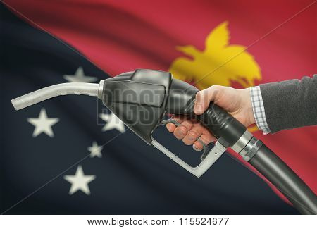 Fuel Pump Nozzle In Hand With National Flag On Background - Papua New Guinea