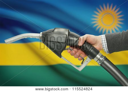 Fuel Pump Nozzle In Hand With National Flag On Background - Rwanda