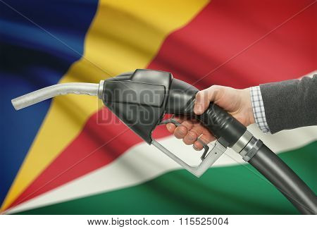 Fuel Pump Nozzle In Hand With National Flag On Background - Seychelles