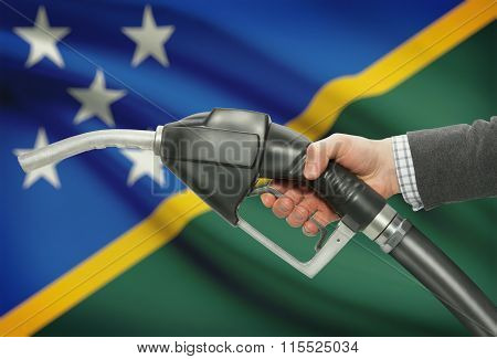 Fuel Pump Nozzle In Hand With National Flag On Background - Solomon Islands