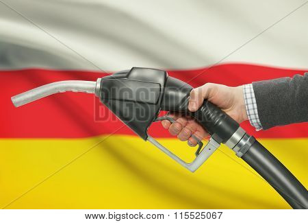 Fuel Pump Nozzle In Hand With National Flag On Background - South Ossetia