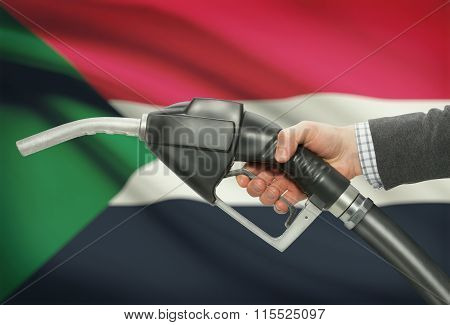 Fuel Pump Nozzle In Hand With National Flag On Background - Sudan