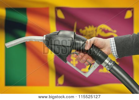 Fuel Pump Nozzle In Hand With National Flag On Background - Sri Lanka