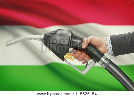 Fuel Pump Nozzle In Hand With National Flag On Background - Tajikistan