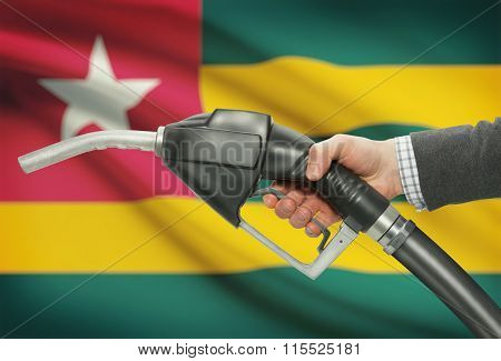 Fuel Pump Nozzle In Hand With National Flag On Background - Togo