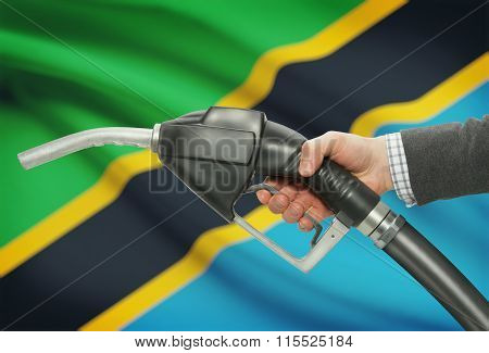 Fuel Pump Nozzle In Hand With National Flag On Background - Tanzania