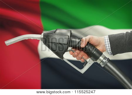 Fuel Pump Nozzle In Hand With National Flag On Background - United Arab Emirates