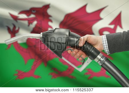 Fuel Pump Nozzle In Hand With National Flag On Background - Wales