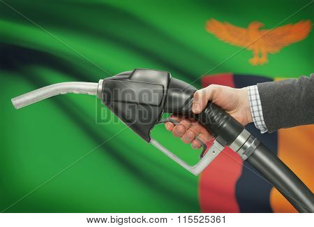 Fuel Pump Nozzle In Hand With National Flag On Background - Zambia