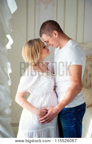 Love And Happy Pregnancy.gentle Beautiful Pregnant Couple Near Tulle Curtains